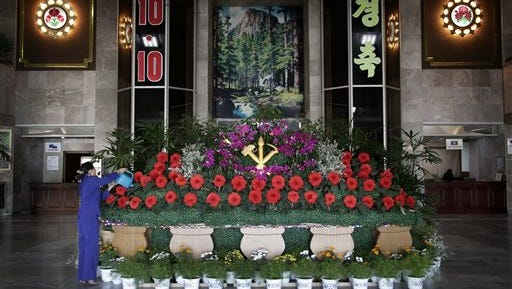 A hotel worker waters a flower display for the 70th anniversary of the founding of North Korea's Workers' Party, Friday, Oct. 9, 2015, ahead of celebrations on Oct. 10. (AP Photo/Wong Maye-E)