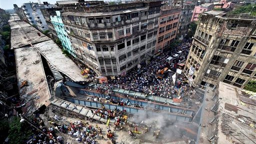 Locals and rescue workers clear the rubble of a partially collapsed overpass Thursday in Kolkata, India. Rescuers dug through large chunks of debris from the overpass that collapsed while under construction Thursday, killing many people and injuring scores of others, officials said.