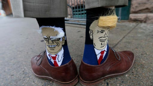 Colorado Gov. John Hickenlooper shows off his socks--one with Democratic presidential candidate Bernie Sanders and the other with Republican candidate Donald Trump--before entering his former brewpub for a book signing event to mark the release of his autobiography Thursday, May 26, 2016, in Denver. Hickenlooper, who is term-limited, is doing book talk rounds this week, reviving speculation that he is positioning himself to join Hillary Clinton's presidential campaign ticket. (AP Photo/David Zalubowski)