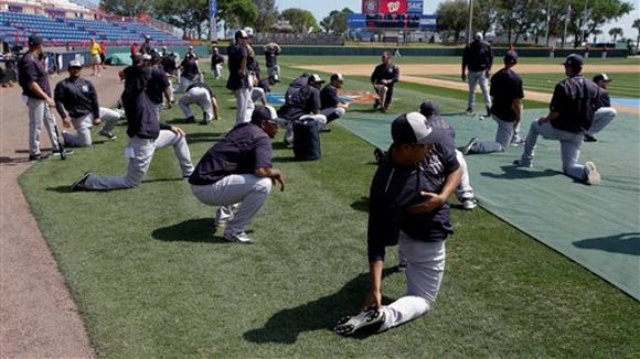New York Yankees payers stretch as they warm up before a spring training baseball game against the Washington Nationals, Wednesday, March 23, 2016, in Viera, Fla.