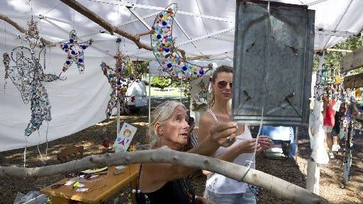 "Terri Finethy (left), seen here speaking with customer Nicolett Connelly, of Vero Beach, is one of nearly 70 vendors participating in the Treasure Coast Pilot Club's 28th annual Autumn In The Park at Riverside Park in 2015. ""I am a junk artist. I put pieces and parts of things together and everybody says it makes them happy, "" said Finethy, of Vero Beach. ""I love doing this show."""
