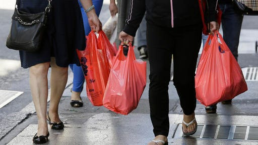 FILE - In this Sept. 20, 2016, file photo, women walk with plastic bags through Chinatown in San Francisco. California voters have narrowly approved a statewide ban on single-use plastic carryout bags. Proposition 67 was placed on the November 8, 2016, ballot by plastic bag industry supporters to try to overturn a ban approved by the state legislature two years ago.