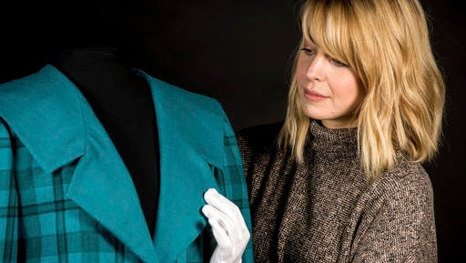"""In this photo provided by Historic Royal Palaces, a conservator handles a blue tartan jacket designed by the Emanuels which was worn by Princess Diana, during an official visit to Venice in 1985. Kensington Palace says a new exhibition tracing the evolution of the late Princess Diana's style is set to open in February. The palace said Tuesday, Nov. 15, 2016 that the exhibition, """"Diana: Her Fashion Story,"""" will follow from the ruffled blouses in her first appearances to her later life. It's the first palace exhibition in a decade to focus solely on the princess."""