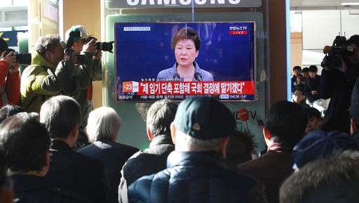 People watch a TV screen showing the live broadcast of South Korean President Park Geun-hye's addressing to the nation, at the Seoul Railway Station in Seoul, South Korea, Tuesday, Nov. 29, 2016. The embattled South Korean president says she'll resign if parliament comes up with a plan for the safe transfer of power.