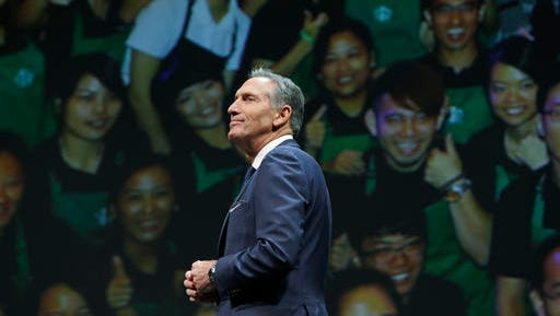FILE - In this Wednesday, March 23, 2016, file photo, Starbucks CEO Howard Schultz walks in front of a photo of Starbucks baristas, at the coffee company's annual shareholders meeting in Seattle. Starbucks announced Thursday, Dec. 1, 2016, that Schultz is stepping down from the coffee chain that he joined more than 30 years ago, and that Kevin Johnson will become chief executive as of April 3, 2017. Schultz will become executive chairman on that date to focus on innovation and social impact activities, among other things.