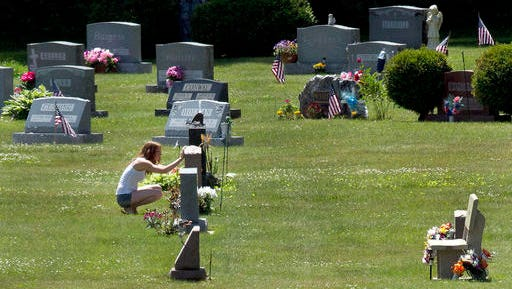 FILE - In this June 17, 2016 file photo, Erika Marble visits the gravesite of Edward Martin III, her fiancé and father of her two children, in Littleton, N.H. The 28-year old died Nov. 30, 2014, from an overdose of the opioid Fentanyl. Drug overdose deaths increased by 33 percent in the past five years across the U.S. as of 2016. New Hampshire saw a 191 percent increase while Massachusetts, North Dakota, Connecticut and Maine saw death rates jump by more than 100 percent.