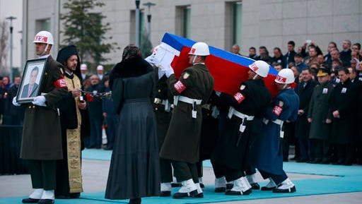 Members of a Turkish forces honour guard carry the Russian flag-draped coffin of Russian Ambassador to Turkey Andrei Karlov who was assassinated Monday, as an officer, left, holds his picture during a ceremony at the airport in Ankara, Turkey, Tuesday, Dec, 20, 2016. Turkey and Russia are more committed than ever to advance peace efforts in Syria, the two countries' foreign ministers declared Tuesday, a day after the killing in an attack both countries described as an attempt to disrupt their improved ties.