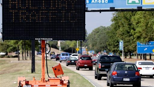 FILE - In this Nov. 20, 2012 file photo, a sign alerts travelers to expect holiday traffic at George Bush Intercontinental Airport in Houston. During the long 2014 holiday weekend, 46.3 million Americans are expected to go 50 miles or more from home, the highest number since 2007, according to travel agency and car lobbying group AAA. That would be a 4.2 percent increase over last year. (AP Photo/David J. Phillip, File)
