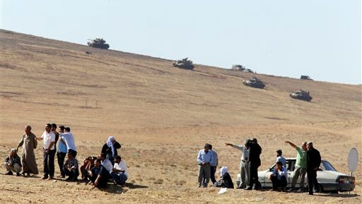 Turkish Kurds watch the fighting over the border, as in the background Turkish army tanks hold their positions on a hilltop in the outskirts of Suruc, at the Turkey-Syria border, overlooking Kobani in Syria where fighting had ben intensified between Syrian Kurds and the militants of Islamic State group, Monday, Oct. 6, 2014. Kobani, also known as Ayn Arab and its surrounding areas have been under attack since mid-September, with militants capturing dozens of nearby Kurdish villages. (AP Photo/Lefteris Pitarakis)