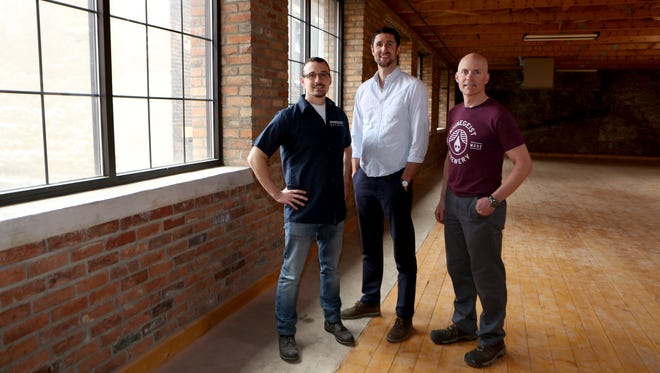 Rhinegeist founders Bob Bonder (left) and Bryant Goulding stand with brewer Jim Matt (right) in the new event space at Rhinegeist.