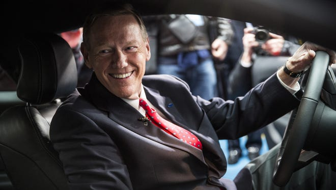 """Alan Mulally, then the CEO of Ford, poses inside the 2015 Ford Mustang on the set of """"Good Morning America"""" in December  2013 in New York."""