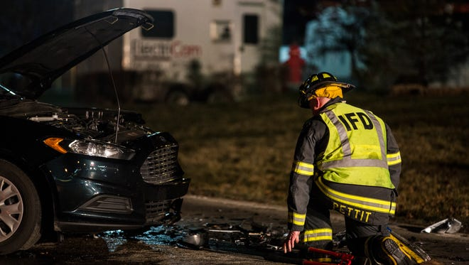 An Indianapolis firefighter kneels in front of the vehicle that struck two of his fellow firemen on Jan. 27, 2016.