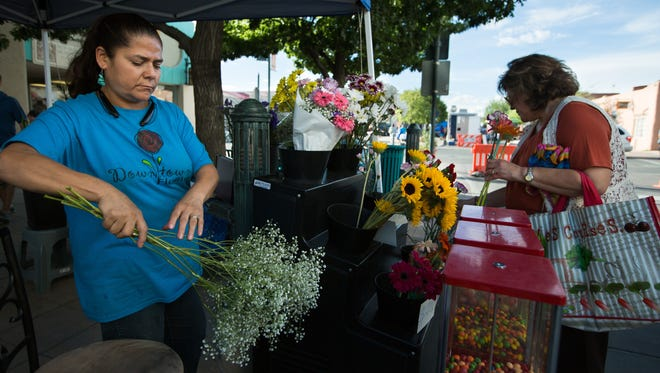 Owner of Downtown Florist Natalie Sanchez, left, separates Baby's-breath flowers for Glenda Rodriguez, August 10, 2016, during evening Farmer's Market.