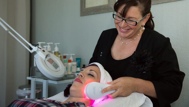 Kim Michele Magenheim, right, uses a LightStim LED light therapy for acne on Karey Flores, Sept. 16, 2016, at her skin care studio located inside Billy the Kid Hair Designs.