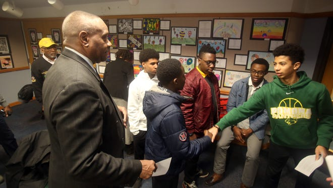 Jaden Herrera, 13, right, greets Zachary Colimon, 14, at the start of an Omega Psi Phi Fraternity Black History Month mentoring program session at the Finkelstein Library in Spring Valley Feb. 12, 2017. Watching at left is Gerald H. Inman, Sr., the chairman of the fraternity's Rockland Omega Academy mentoring program. The mentoring program was established to provide academic and cultural enrichment opportunities to minority boys in Rockland County. The program focuses on skills such as computer, public speaking, etiquette training, and financial literacy.