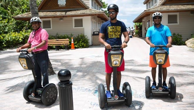 Bipin Patel, from left, Malak Patel, and Rajesh Patel, all of Ocala, Fla., stop at the Naples Pier during a tour offered by Segway Tours of Naples in August 2016.