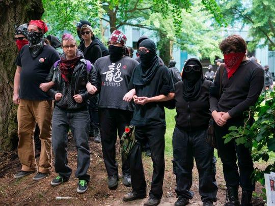 Far-left antifa demonstrators link arms at Chapman