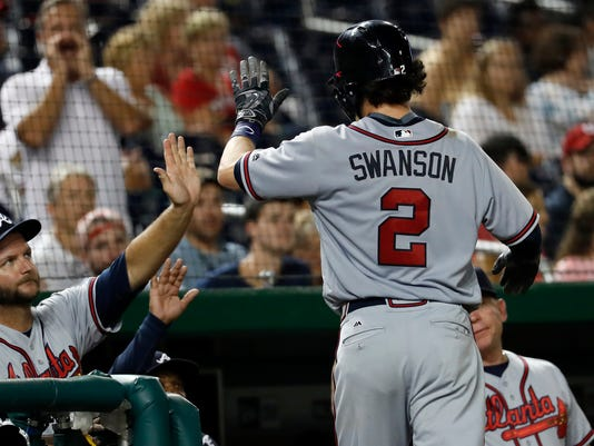 Atlanta Braves' Dansby Swanson is greeted at the dugout after hitting a solo home run iin the seventh inning of a baseball game against the Washington Nationals at Nationals Park, Wednesday, Sept. 7, 2016, in Washington. (AP Photo/Alex Brandon)