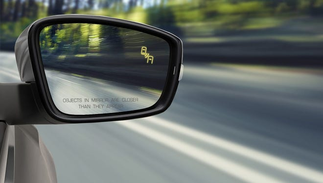 A blind spot monitoring system in this Volkswagen vehicle activates a small, lighted icon in the side-view mirror.