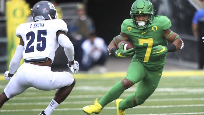 Oregon's CJ Verdell (7) runs down field against Nevada's Daniel Brown, left, during the first quarter of an NCAA college football game Saturday, Sept. 7, 2019, in Eugene, Ore.