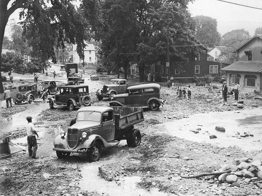 Debris covers State Street at the base of West Hill after flooding in 1935. This photograph shows the area originally known as the octopus intersection, where State, Buffalo, Cliff, Hector and Elm streets met.