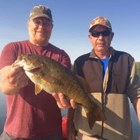 Jim Pones Jt. and Jim Pones Sr. behind a nice walleye.