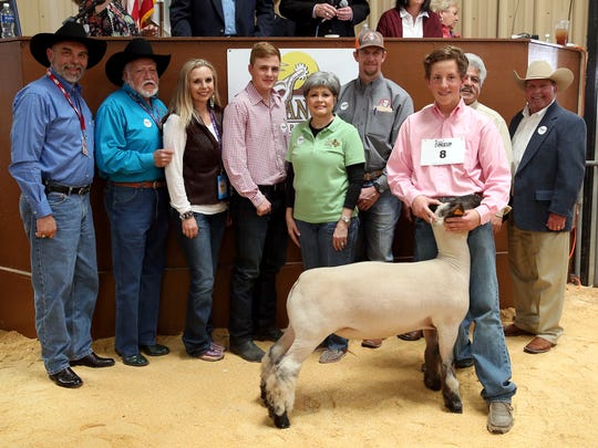 Will Peters, Kendall Co. 4-H, sold the reserve grand champion market lamb for $9,000. Pictured are Micheal Strauss, H-E-B; Clay Cross, Cross Country Construction; Bridget Carr, Carr Clinic; Ryan Gandy, Gandy Ink; Toni Sudduth, Trans Texas Southwest Federal Credit Union; Joe Self, Automatic Fire Protection; Peters; Raymond Meza, Twin Mountain Fence; and Todd Price, Jim Bass Cars and Trucks.