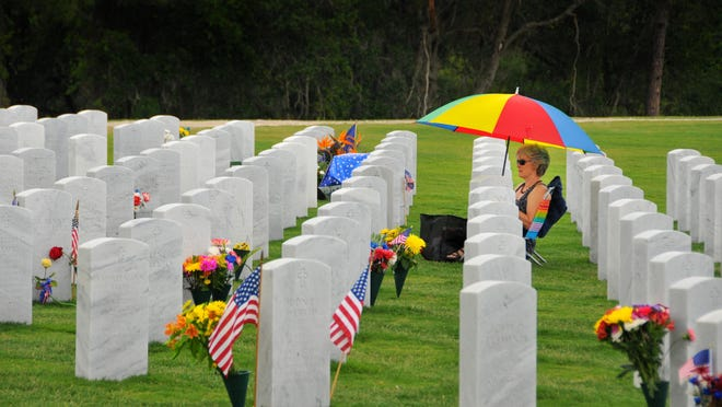 Dawn Young of Viera sat alone by her father's grave during a Memorial Day ceremony in May at Cape Canaveral National Cemetery near Scottsmoor in 2016.