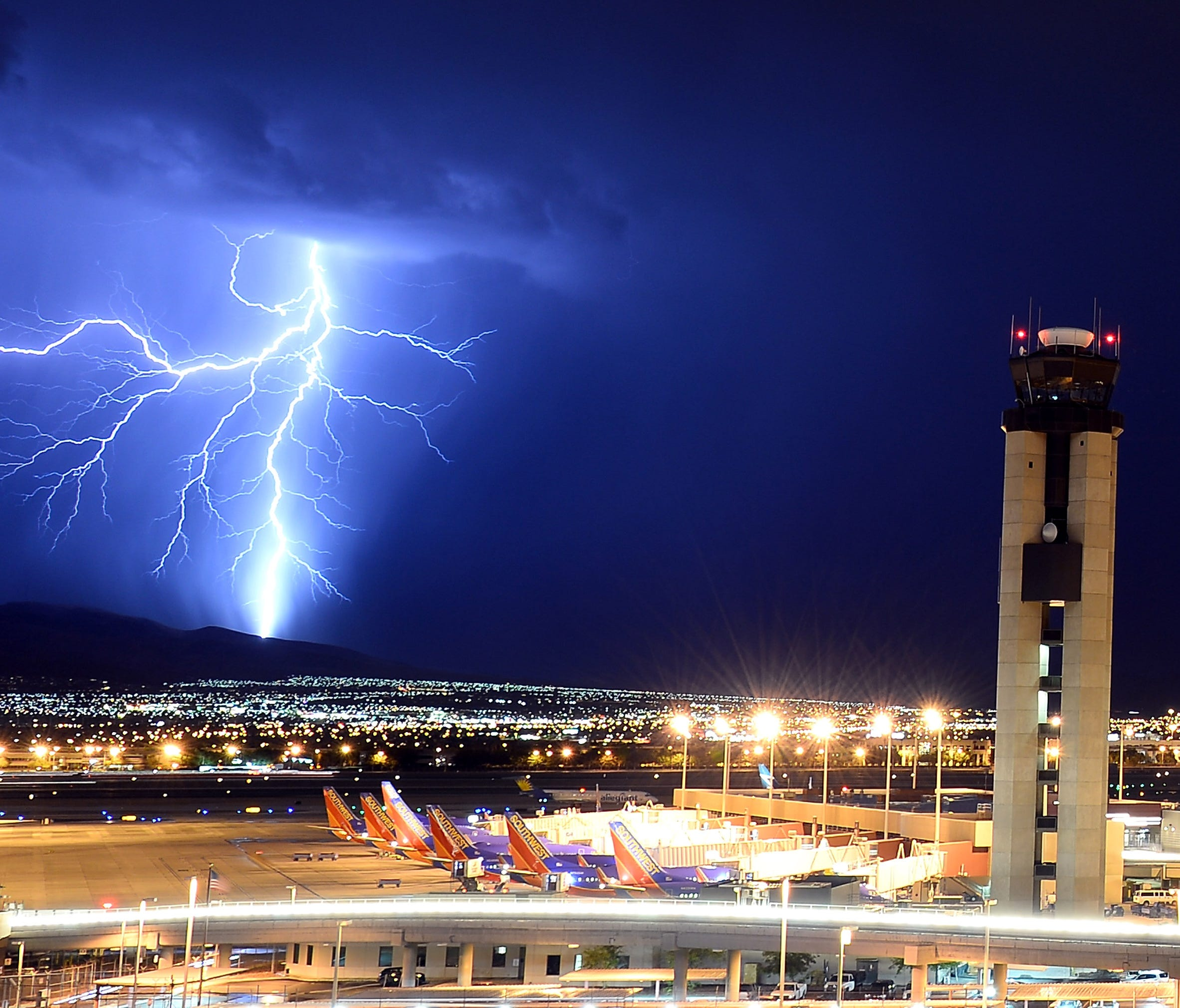 Lightning flashes behind an air traffic control tower at Las Vegas McCarran International Airport on Aug. 18, 2013.