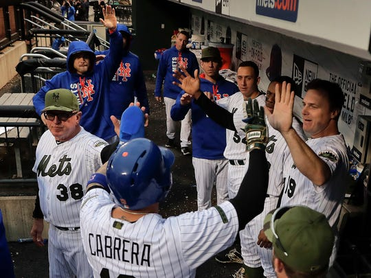 New York Mets' Asdrubal Cabrera is greeted by teammates and coaches after scoring a run against the Milwaukee Brewers during the sixth inning of a baseball game, Monday, May 29, 2017, in New York.