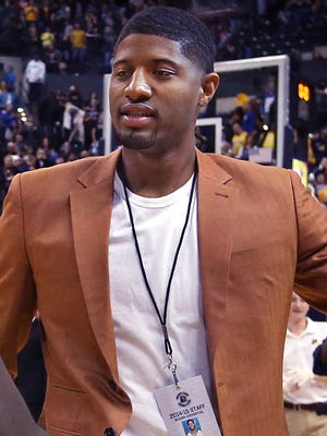 """It's all a joke, but Indiana Pacer Paul George has a 2014-15 season press credential that reads """"Young Trece Pacers PR intern,"""" thanks to Pacers media relations director David Benner, who has officially credentialed him as a public relations intern for the entire season. George, whose broken leg is on the mend, sits at the press table during games as a safety precaution, instead of on the Pacers bench, to make sure his leg is out of harm's way. George, wearing the credential at the Charlotte Hornets game Wednesday, Nov. 19, 2014, greets former teammate Lance Stephenson."""