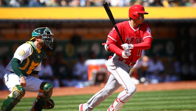 Shohei Ohtani follows through after hitting a single in his first major league at bat against the Oakland Athletics on Thursday.