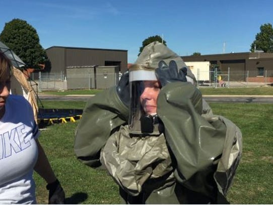 Tech Sgt. Sabrina Roberts at right puts on her chemical