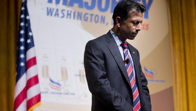 Louisiana Gov. Bobby Jindal, left, bows his head on stage as he leads a prayer for the victims of recent Charleston church shooting before speaking at the Road to Majority 2015 convention in Washington, Friday, June 19, 2015. (AP Photo/Pablo Martinez Monsivais)