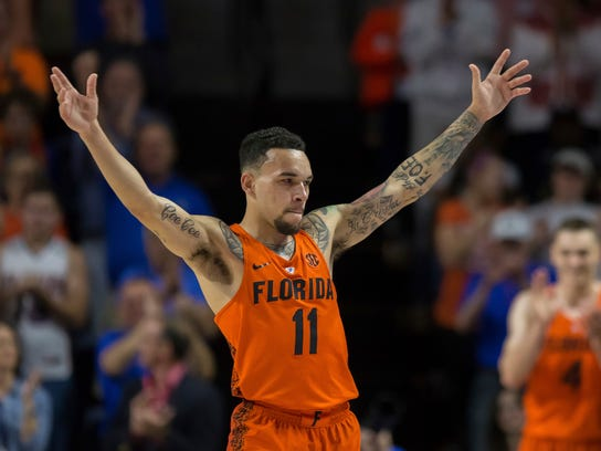 Florida guard Chris Chiozza (11) acknowledges the crowd as he leaves the game in the final minute of an NCAA college basketball game against Kentucky in Gainesville, Fla., Saturday, March 3, 2018. Florida won 80-67. (AP Photo/Ron Irby)