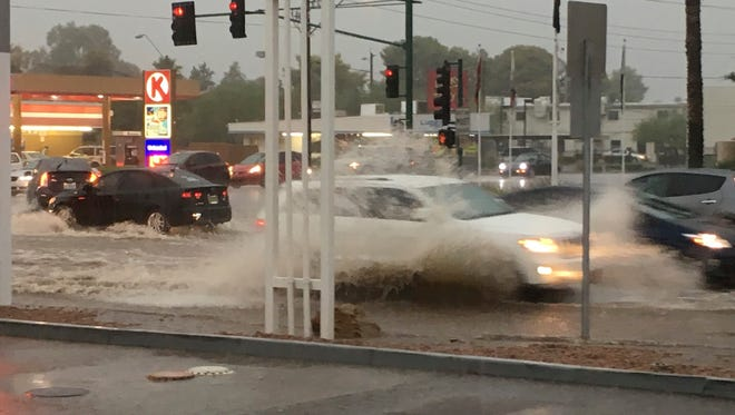 In this photo taken Tuesday, Aug. 2, 2016, cars make their way through a flooded intersection in Phoenix. The desert Southwest is poised to get a second soaking after monsoon rains hit the region, stranding drivers, flooding streets and prompting water rescues. The rains bring some relief to crews fighting wildfires, but also the potential for mudslides in areas blackened by flames.