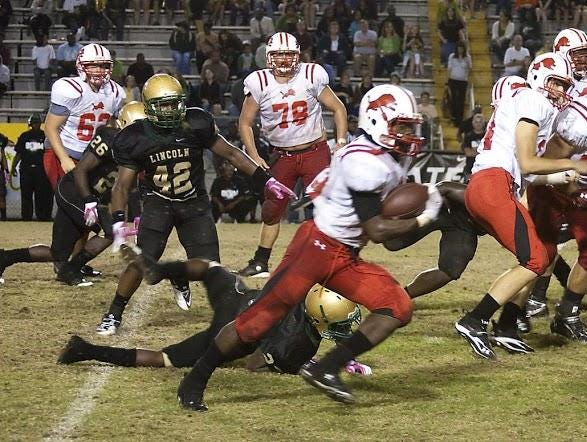 Leon alum Trey Braun (78) watches in the background as running back Tim Longmire finds ground to gain against Lincoln in a 2010 game.