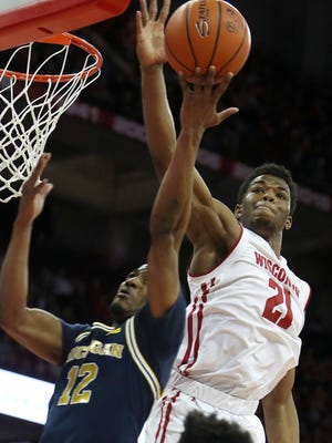 Wisconsin guard Khalil Iverson (21) blocks a shot from Michigan guard Muhammad-Ali Abdur-Rahkman on Sunday, Feb. 11, 2018, in Madison, Wis.