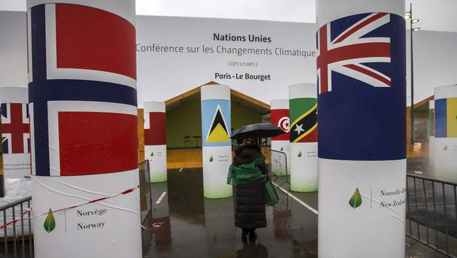 A man walks past pillars bearing national flags at the entrance of the COP21 Climate Conference venue in Le Bourget, north of Paris, on Nov. 24.