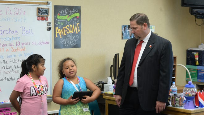 Richmond Community Schools Superintendent Todd Terrill listens to summer school students describe their project using a tablet.