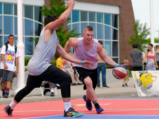 Brad Biskaborn, of London, Ont, tries to dribble around Tyler Conklin, of Chesterfield, Sunday, May 24, during the annual Gus Macker basketball tournament in Port Huron.