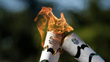 Handout picture released by the Rio 2016 Olympic Committee showing transaction of flames of the Olympic torches in Pirenopolis, Goias State, Brazil, on May 5, 2016.