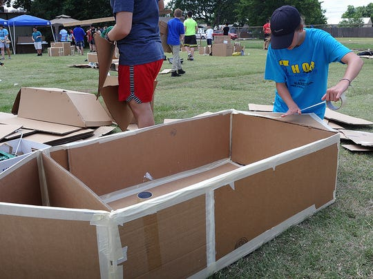 Avery Boyle seals a joint with masking tape on the cardboard boat she and her team are constructing for the annual Barwise Boat Float, Thursday morning at Wood Memorial Park on Maplewood. The students can use only cardboard, caulk, masking tape and paint for the build.