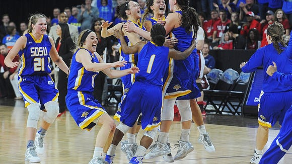 SDSU players celebrate their 61-55 win over USD in the Summit League women's basketball tournament championship game Tuesday in Sioux Falls.