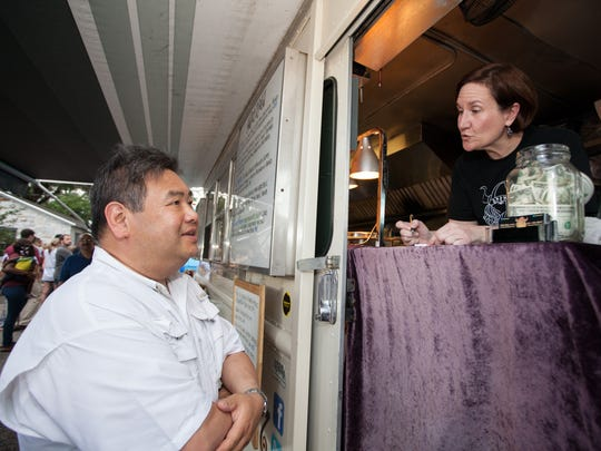 Eric Fan orders food from Beverly Rich, an owner of