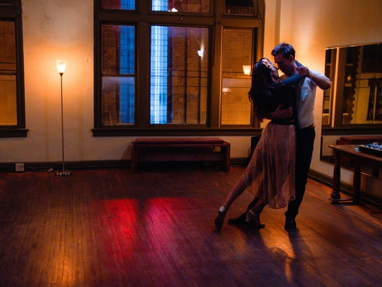 """A scene from """"Ctrl+Alt+Dance"""" filmed at Covington's Step-N-Out Dance Studio on Madison Avenue; the neon marquee of Madison Theater is visible through the window. The film will premiere at Memorial Hall in Over-the-Rhine on Feb. 13 and 14."""