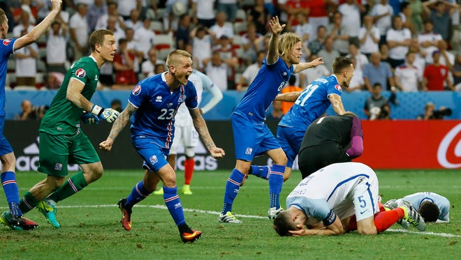 Iceland players celebrate at the end of their round of 16 soccer match against England on Monday.