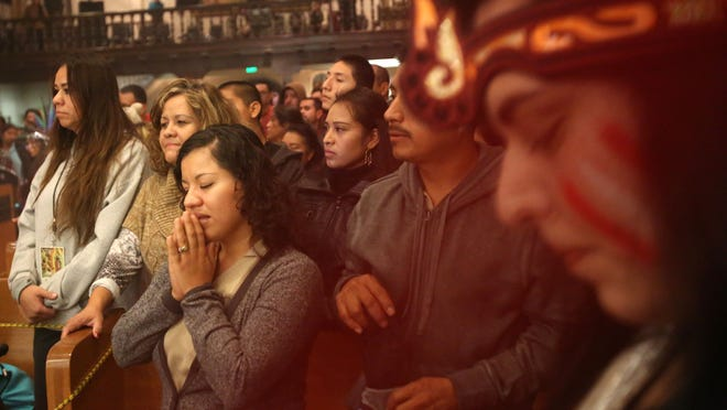Catholics sing and pray prior to the start of the Virgen de Guadalupe procession Friday.
