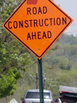 A highway sign warns of road work ahead.