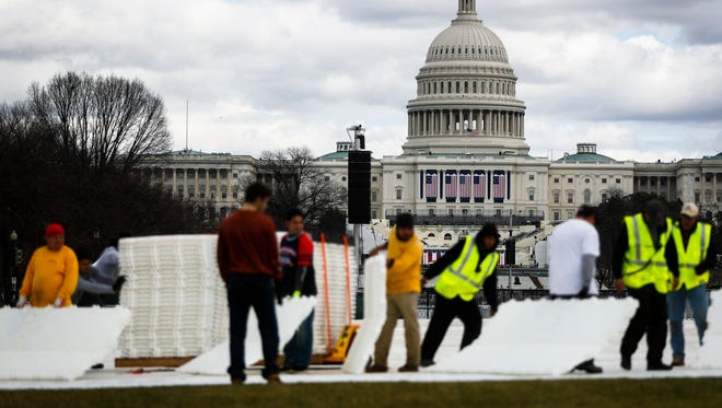 Workers place plastic flooring on the grass of the National Mall in Washington, Wednesday, Jan. 18, 2017, as preparations continue for Friday's presidential inauguration.